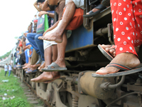 Bangladeshi travelers ride on over crowded train