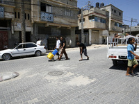 Displaced Palestinian children collect water from U.N.