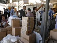 Palestinians receive their monthly food aid at a U.N.